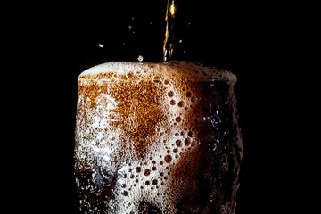 Soda large glass, overflowing glass of soda closeup with bubbles isolated on black background