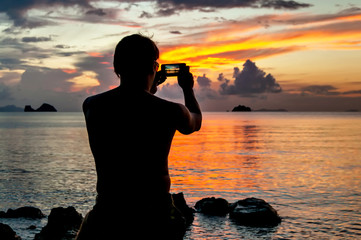 Man standing on the rock of a tropical island and watching the sunset