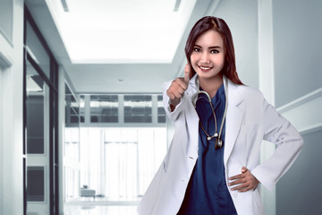 Pretty asian doctor smiling with hospital background