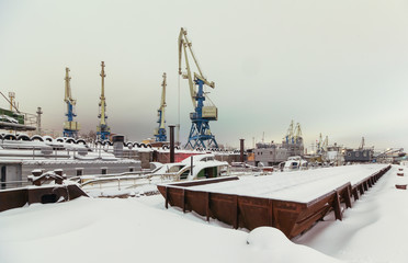 Night view of harbor cranes on the waterfront of the port covered with snow. Focus on the central crane