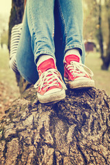 Woman's legs wearing red canvas sneakers and blue jeans, sitting on a tree, retro styled photo