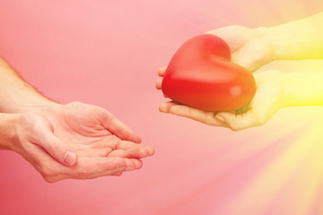 Fototapete - Female and male hands with red heart on pink background