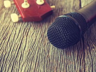 Black microphone on wooden plate with guitar