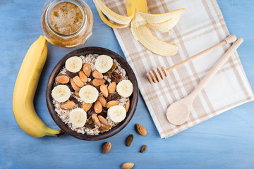 Healthy breakfast. Granola with nuts and  banana in a wooden bowl, honey and  milk  on a blue  background
