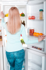 Young blonde at home near fridge