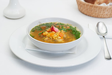 Lentil Soup Served in a White Bowl with Spoon on a restaurant table