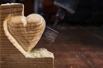 sanding wood in heart shape with a rotary tool