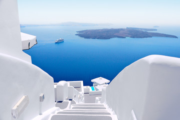 Fotobehang Santorini White wash staircases on Santorini Island, Greece. The view toward Caldera sea with cruise ship awaiting.