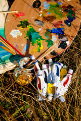 Artist's Palette with paints and brushes on grass background