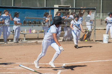 Filipino softball batter running to first base.