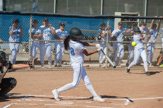 Filipino softball batter hitting a line drive.