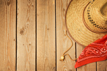 Cowboy hat with red bandanna on wooden rustic background. View from above
