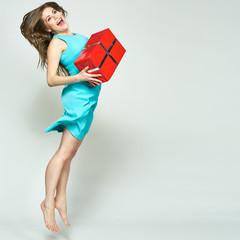 Jumping woman holding gift box.