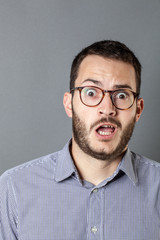 scared young bearded businessman with eyeglasses expressing amazement and fear