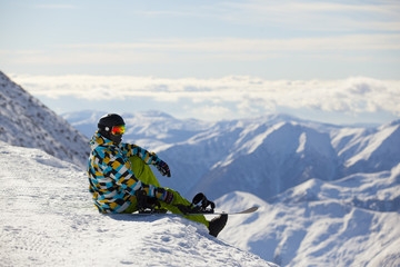 Snowboarder looking at mountains sitting on mountain top