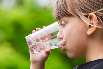Girl drinking glass of fresh water