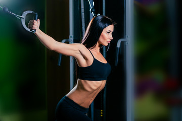 young fitness woman execute exercise with exercise-machine Cable Crossover in gym, horizontal photo
