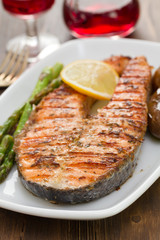 salmon with lemon and vegetables on white dish