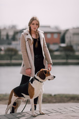 Young hipster girl with her pet estonian hound dog playing and having fun outdoor in the park.