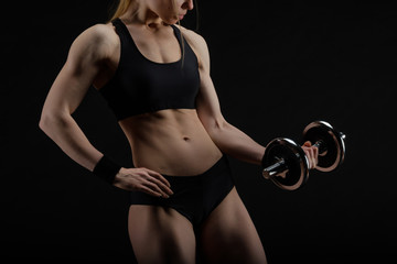 Young slim strong muscular woman posing in studio with dumbbell