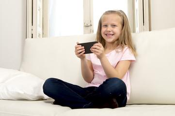 happy blond little girl on home sofa using internet app on mobile phone