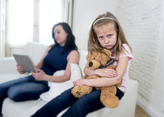 young internet addict mother using digital tablet pad ignoring little sad daughter