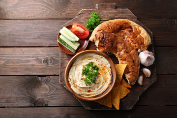 Wooden bowl of tasty hummus with chips, flat bread and parsley on table