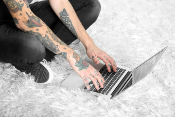 Young man with tattoo using laptop on a floor at home