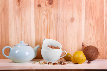 Teapot with cups, nuts and pears on wooden background