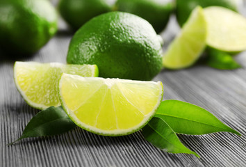 Limes and slices on wooden table, closeup