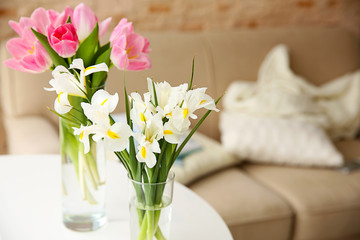 Beautiful fresh tulips and irises on table, indoors
