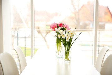 Beautiful tulips and irises on dinning table on window background