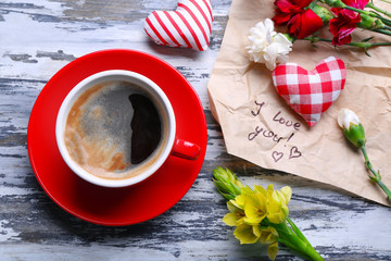 Cup of coffee with flowers and textile hearts on wooden background