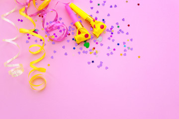 Blowers, streamers and confetti on pink background