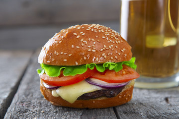 Fresh and juicy hamburger with a beer on wooden table.