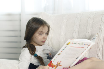 teenager girl reads a book while sitting in a chair