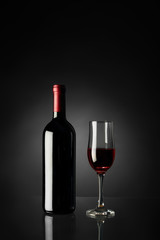 Glass of red wine and bottle on a black background