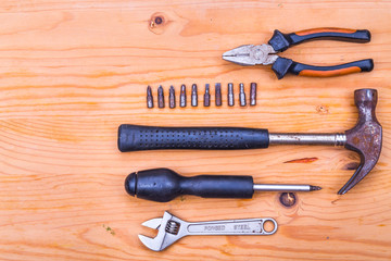 Essential basic tools set consisting hammer, plier, screwdriver and adjustable crescent on wooden background