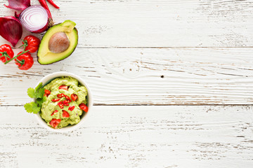 Guacamole with avocado and tomatoes mexican food. white wooden background