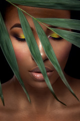 Beautiful woman portrait on black background. Young afro girl posing with green leaves and  closed eyes. Gorgeous make up. Pure skin