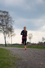 Hübsche Frau im Frühling, joggen auf einem Schotterweg