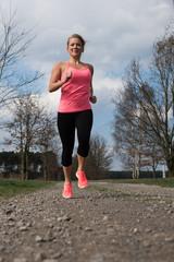 Frau im pinken Top läuft auf einem Schotterweg entlang