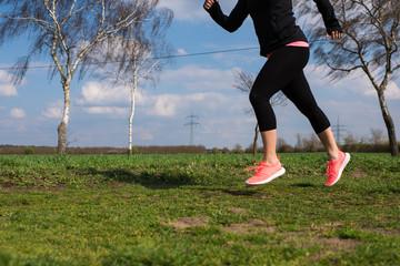 Joggerin läuft auf einer Wiese im Frühling