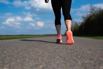 Joggen in pinken Laufschuhen auf asphaltierter Strasse