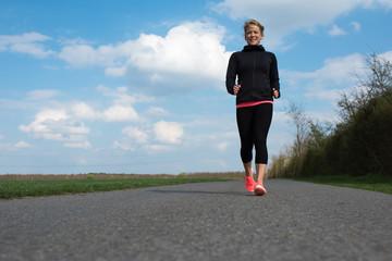 Joggen im Frühling auf einer Straße, Sportliche Frau in Leggings beim Joggen