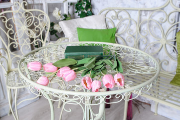 pink tulips and book lying on metal table vintage