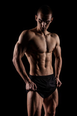 Sexy Athletic Man showing six pack abs. Isolated on black background with copyspace
