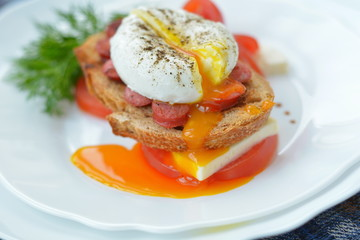 Bright poached eggand sandwich - breakfast in restaraunt