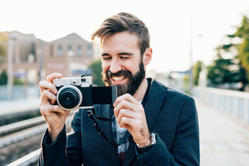 young handsome caucasian bearded man taking photograph