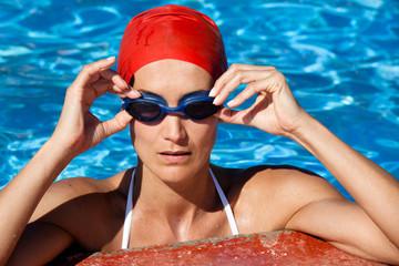 femme dans l'eau au bord d'une piscine avec un bonnet et des lunettes